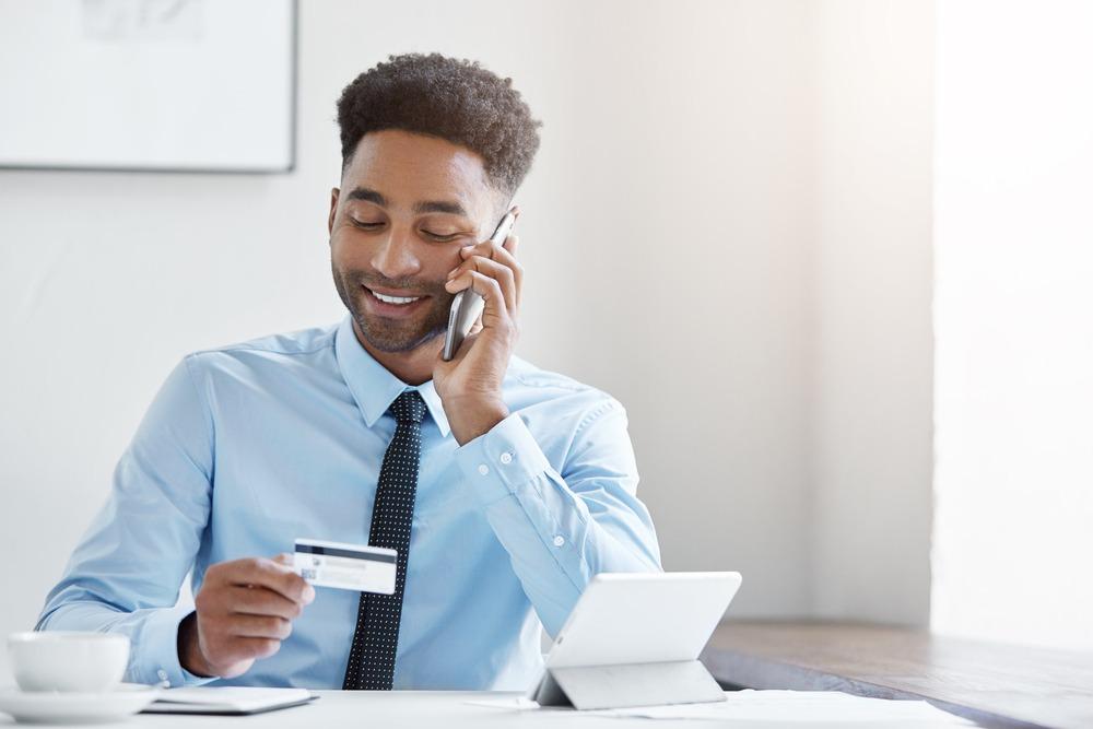 Businessman talking smartphone paying bill credit card webcallback